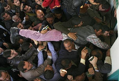 图文:巴勒斯坦年轻人奋力将护照伸进窗口