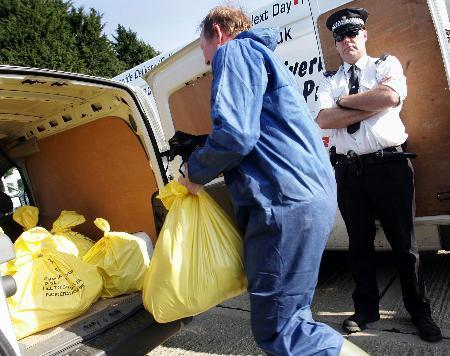 图文:英国男子将装有鸡只的塑料袋放入货车