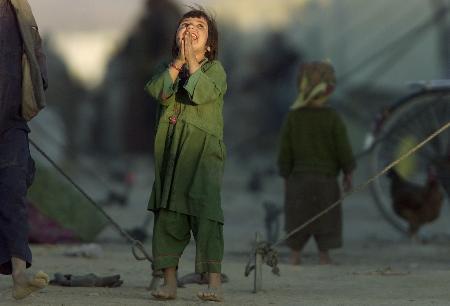 一名阿富汗女孩仰望天空的喷气式飞机