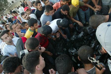 图文:人们在爆炸现场观看被炸汽车的残骸