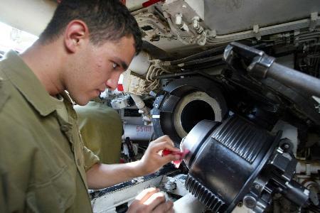 图文:一名以色列士兵在清理炮膛