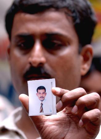 图文:一名男子展示失踪的弟弟的照片