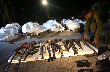 图文:以色列士兵在真主党人员尸体旁整理枪支