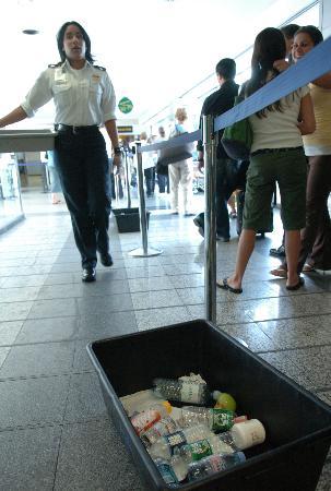 图文:安检人员提醒乘客拿出禁止携带的液体物