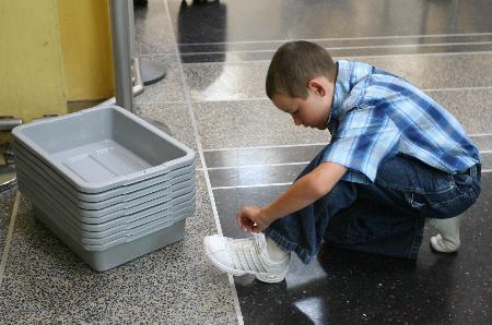 图文:小男孩在脱鞋准备进行安检