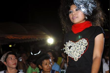 图文:曼谷一名模特展示用安全套装饰的时装