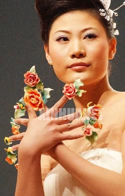 一名模特在美甲比赛中展示以蝴蝶和绿叶为主题的创意美甲作品.图片