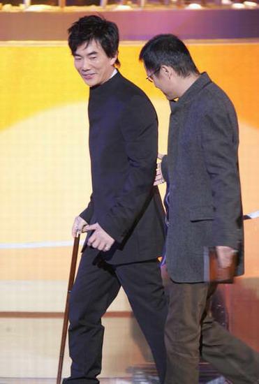 图文:任贤齐微笑拄拐上台为最佳电影音乐颁奖
