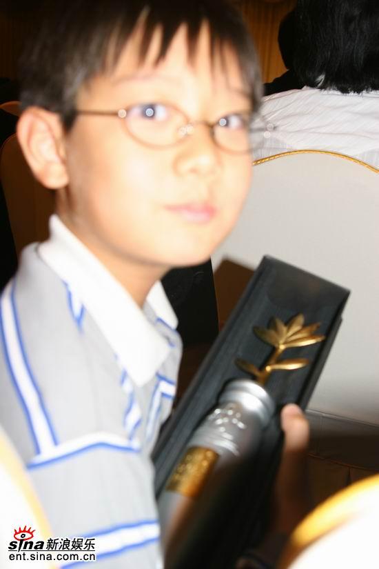 图文:影评人颁奖-奉俊浩幼子展示父亲所获奖杯