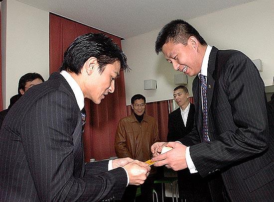 图文:新浪CEO兼总裁汪延与刘德华交换名片