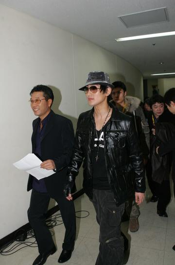 图文:韩国歌手安七炫走进后台众工作人员尾随