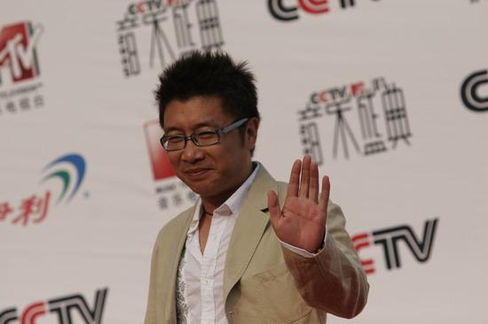 图文:歌手庞龙向大家挥手身着米色西装