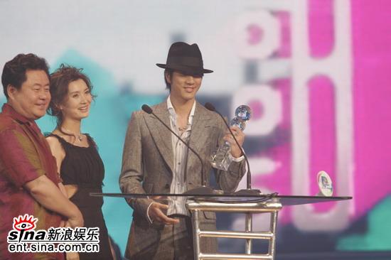 图文:王力宏手举奖杯满脸笑容与观众打招呼