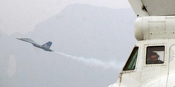 图文:远处掠过的飞机与地上的驾驶员