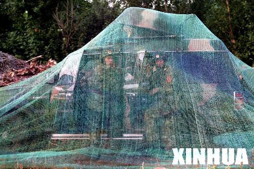 """图文:两名""""红军""""保障人员在经过伪装的车辆内进行通信联络"""