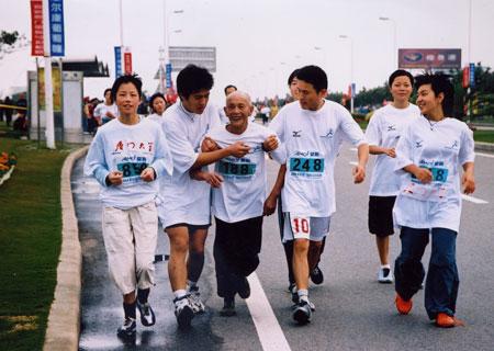 图文-2006厦门马拉松赛运动员搀扶老者