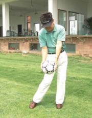 4.下肢主动向前旋转,带动双肩向下运动至击球点,双手的位置与站姿相同,重心在左脚。