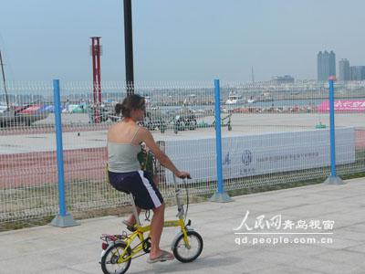 图文-青岛国际帆船赛决赛运动员骑自行车赶往赛场