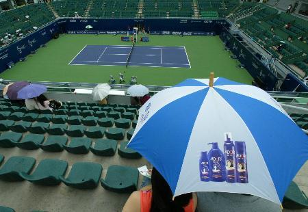 图文-斜风细雨乱中网热情观众打伞待比赛