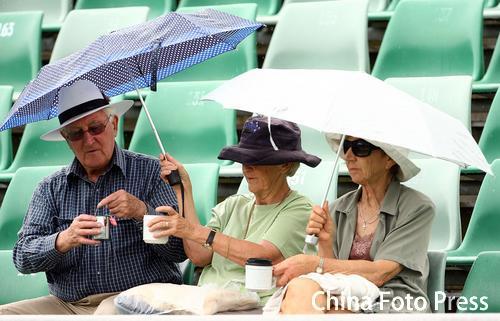 图文-澳网球迷雨中观战雨中撑伞品茶别有情趣
