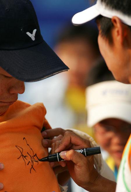 图文-十运会网球混双决赛胜利后李婷给球迷签名